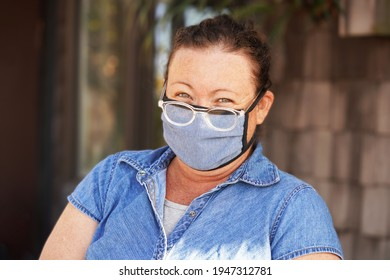 Woman wears mask and reading glasses, as well as a blue denim shirt over a white tank top, outside on a sunny late afternoon with her hair back, smiling