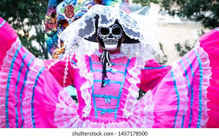 Woman wears sugar skull mask and bright pink Jalisco dress in celebration of Dia de los Muertos / Day of the Dead