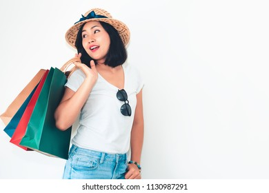 Woman wears white t-shirt and jean is holding many shopping bags in front of bright isolate white background.