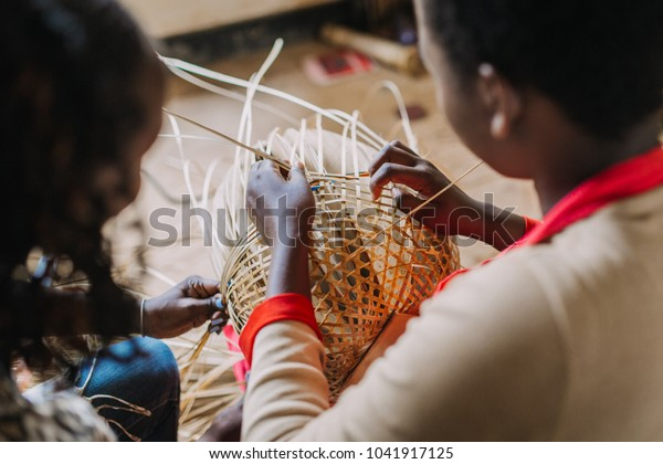 woman weaving a basket out of bamboo in Rwanda Africa