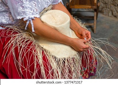 A woman weaving a Panama hat, also known as the traditional brimmed straw hat made of the Toquilla palm, which is on the Unesco Intangible Cultural list and famous from the city of Cuenca, Ecuador.
