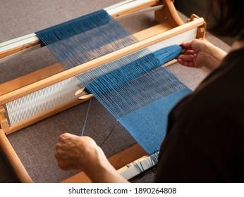 Woman is weaving a weft thread between the warp threads, Single shuttle loom