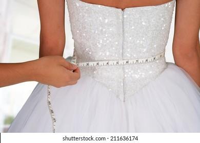 Woman in a wedding dress getting measured