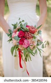 Woman in wedding dress holds a bouquet of pink and red flowers