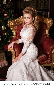 woman in a wedding dress sitting in a luxurious armchair next to decorated Christmas tree