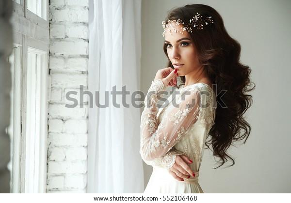Frau in einem Hochzeitskleid, das in der Nähe eines Fensters steht, Haarschmuck