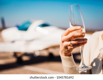 Woman with wedding ring holds glass of champagne standing in the airport