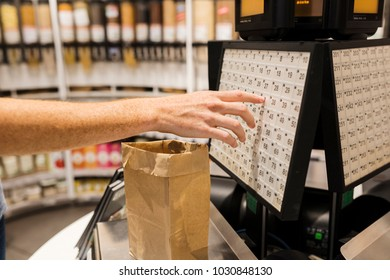 Woman weighing of nuts on electronic scales in bio supermarket