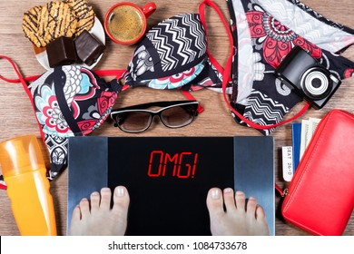Woman weighs herself before vacation. Concept of unhealthy lifestyle and its consequenses. Digital scales with sign omg, holiday accessories and sweets. Top view. Flat lay.