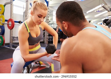 Woman weight training at a gym getting advice from a trainer