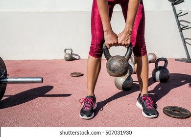 Woman weightlifting kettlebell weight at outdoor fitness gym. Unrecognizable female athlete strength training legs, glutes and back lifting free weights. Closeup of lower body.
