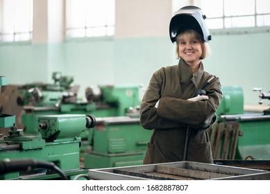 Woman welder with a welding torch in her hands.