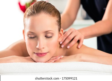 Woman in wellness beauty spa having back massage with essential oil, looking relaxed