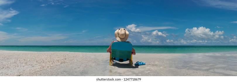 Woman wering sun hat seating in chair sunbathing by waters edge
