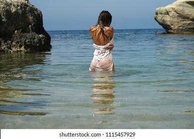 Woman in wet shirt alone in sea - rear view