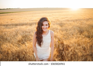 Woman in a wheat field on a summer sunset