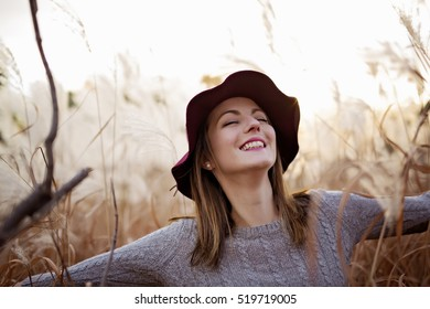 A Woman in a wheat field at sunset with hat
