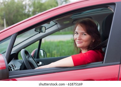 The woman at the wheel the red car