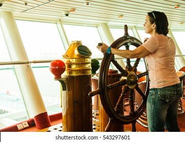 Woman at the wheel of a ship.