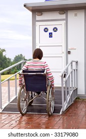 woman in wheelchair drives to a toilet for invalids
