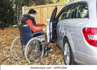 Woman in a wheelchair in the fall next to their car