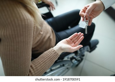 Woman in wheelchair is given keys to house. Getting social housing for disabled people concept
