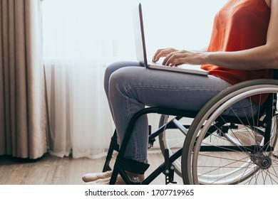Femme en fauteuil roulant à la maison avec un ordinateur portable sur les genoux, main en gros plan