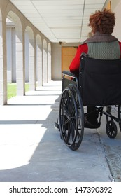 Woman in a wheelchair left in an empty hallway