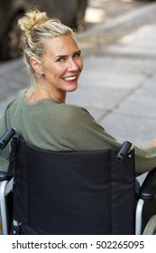 woman in wheelchair outdoors smiling at camera
