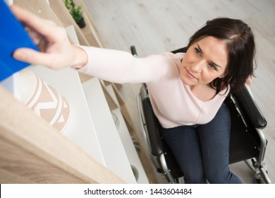 woman in wheelchair reaching for book from high shelf