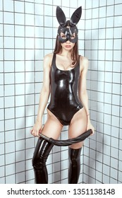 Woman with a whip in her hands. She is wearing a latex bunny suit. The man is wearing a latex suit. BDSM style and humiliation.
