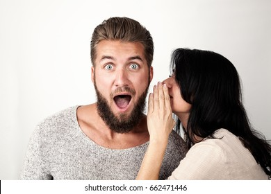 Woman is whispering a secret into her friends ear