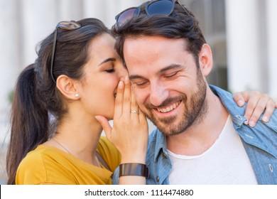 Woman is whispering a secret into his boyfriends ear