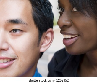 A woman whispers in a mans ear as they watch the world go by.