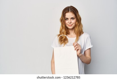 woman with white bag in hand on gray background