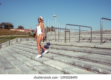 A woman in a white bathing suit body, summer in city goes on street. Longboard skateboard sunglasses. Free space for text. Concept style fashion, lifestyle of young people. Steps up stairs.