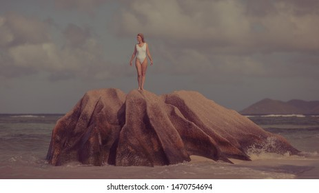 Woman in a white bathing suit on a stone by the sea