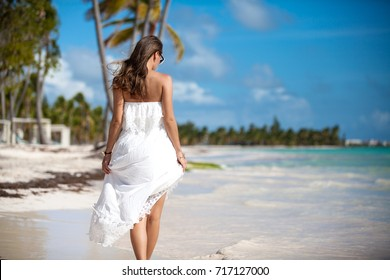 Woman in white beach dress enjoying her summer vacation at resort in the Caribbean island. Elegant sexy female