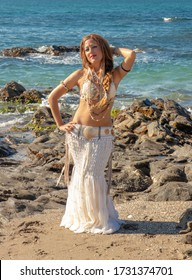 Woman in a white belly dance dress full of ornaments posing on the beach with the rocks and the sea in the background