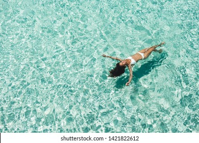 Woman in white bikini lying on transparent turquoise water surface on beach. Travel and vacations concept. Tropical background with empty space