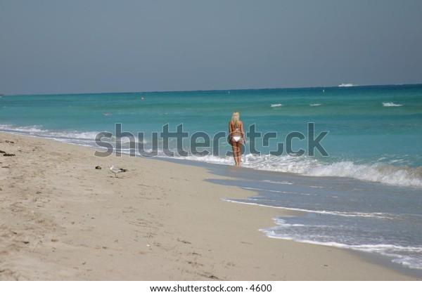 woman in white bikini walking along the beach