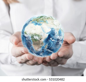 Woman in a white blouse is holding a planet in her hands. Concept of a small world. Elements of this image furnished by NASA