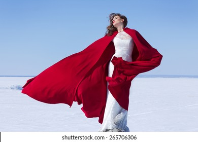 Woman in white bride dress with flying red fabric. Winter background