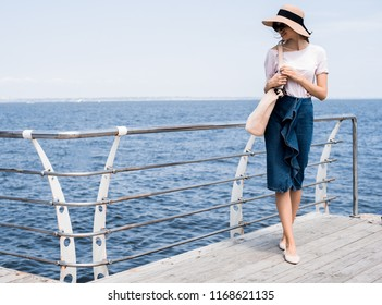 Woman in white casual shirt walking over a wooden jetty in the Maldives, near ocean enjoy summer and every moment. She's happy travaler on new country with comfortable and relaxing mood