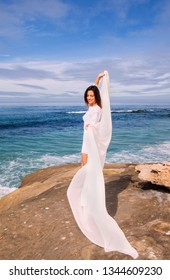 woman in white chiffon by the ocean