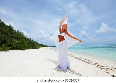 woman with a white cloth in his hands on the beach