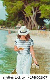 woman in white clothes and fedora hat walking by sea beach