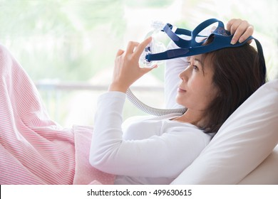 Woman in white clothes laying with knees up in bed  hands holding and wearing CPAP mask . Obstructive sleep apnea therapy.