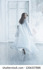 A woman in white clothes leaves the white room in which the snow falls. Marital relations, treason, impotence, divorce - concept. Long exposure, motion effect. Care, separation, separation, illness.