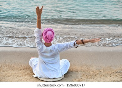 Woman in white clothes and a turban sits on a sandy beach at dawn and practices yoga